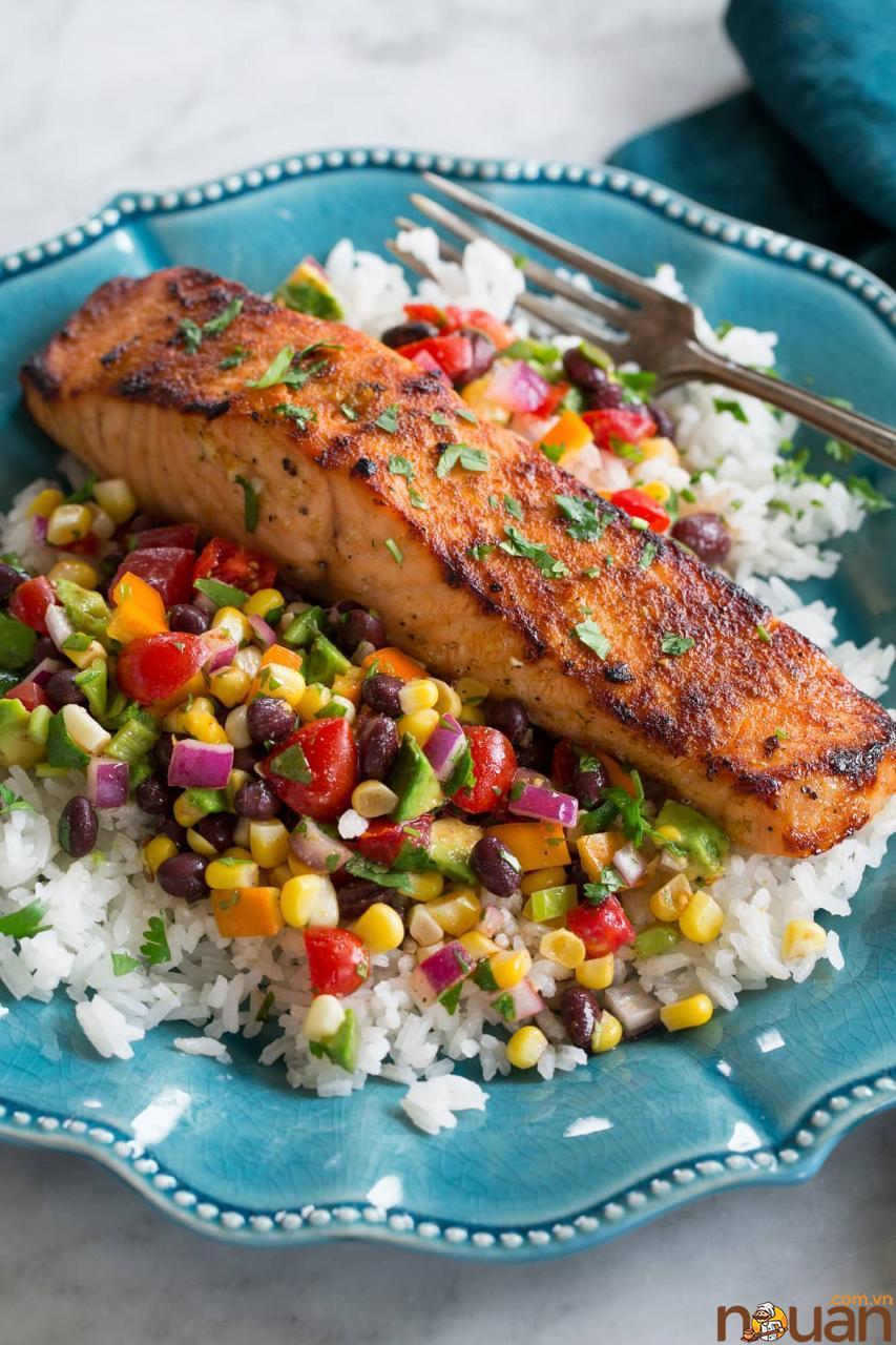 Cá hồi luộc được bày biện trên đĩa salsa ngô đậu đen và cơm trên đĩa màu xanh lam.
