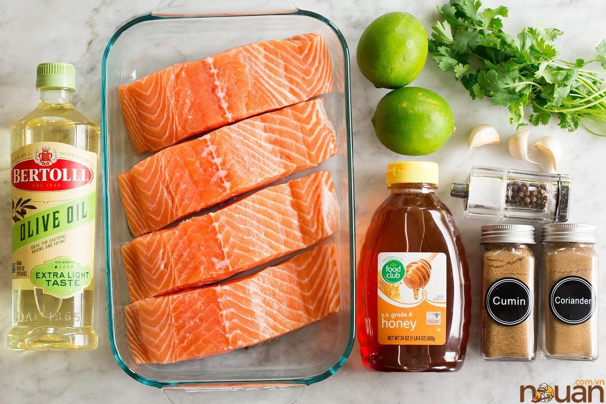 Ảnh trên về các nguyên liệu được sử dụng để làm cá hồi nướng với mật ong, chanh, dầu ô liu, tỏi, ngò và gia vị.